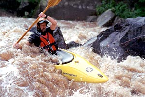 Kayaker paddling through frothy rapid.